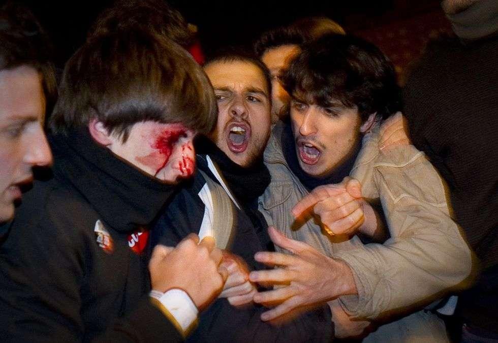 Varios jóvenes ayudan a un compañero que tiene la cara ensangrentada después de ser golpeado por la policía durante la huelga nacional